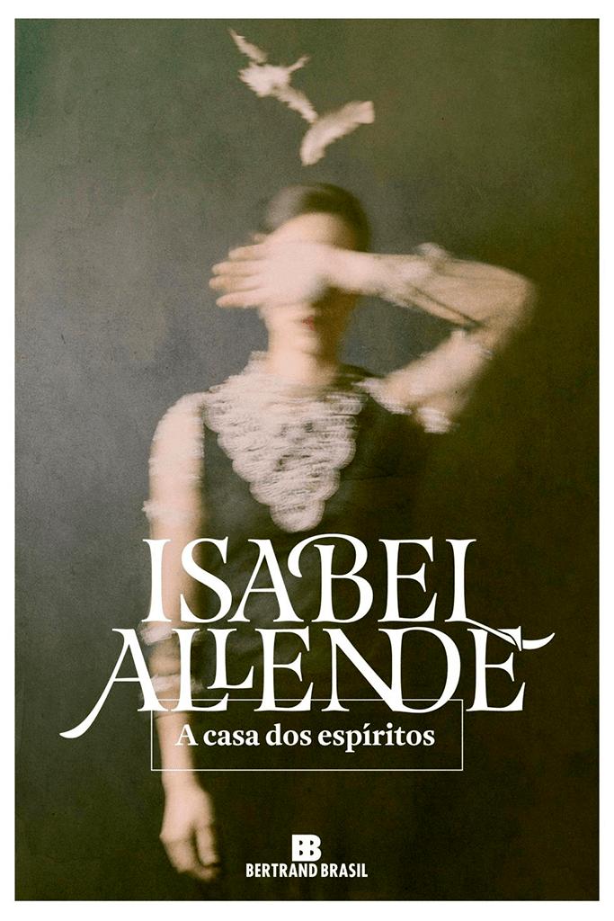 """Na imagem temos a capa do livro A casa dos espíritos que conta com uma foto de uma mulher com roupas de outra época cuja mão está sobre os olhos, acima de sua cabeça vemos algumas penas flutuando e a imagem está um pouco manchada como se fosse uma foto antiga. Na parte inferior temos o título """" A Casa dos Espíritos"""" e o nome da autora """"Isabel Allende"""" em branco. A história do livro acompanha várias gerações de uma família cujos conflitos se misturam ao cenário da política do Chile dos anos 60 e 70."""